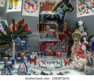 Christmas decoration with wooden horses, dwarfs, dolls, candles, Christmas tree branch and decorative clock.