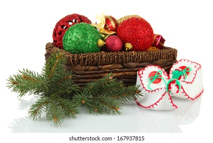 Christmas decorations in basket and shoes isolated on white
