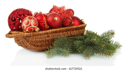 Christmas decorations in basket and spruce branches isolated on white