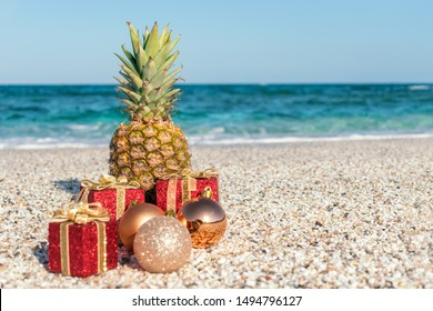 Christmas decorations, baubles and pineapple on a sandy beach on a bright and sunny day. New Year concept.