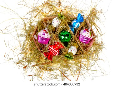 Christmas decorations in a box in the straw. Isolated.