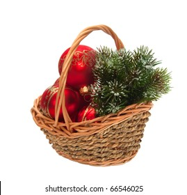 Christmas decorations and a branch of pine in a wicker basket