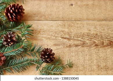 Christmas decorations - branches of coniferous trees with decorations on a wooden background.