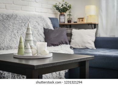Christmas decorations with candle on coffee table in living room near couch closeup
