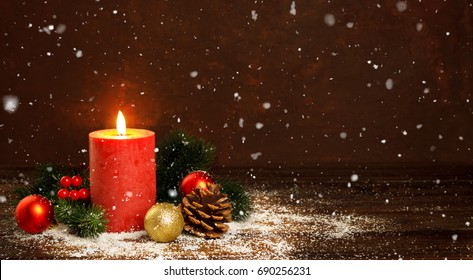 Christmas decorations with festive ornaments on rustic wooden background and snow, red candle, gift boxes with copy space top view