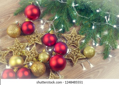 Christmas decorations with fir branches on wooden background, balls and stars, gold and red