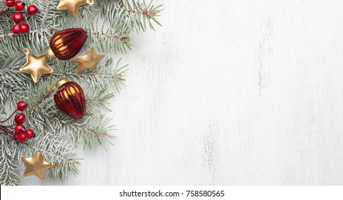 Christmas decorations and fir tree on white shabby wooden background.