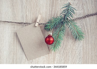 Christmas decorations with a fir-tree and blank card hanging over wooden background