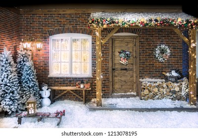 Christmas decorations front of the house with Christmas trees, firewood, a bench, a wreath, a snowman and slay