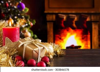 Christmas decorations, a gift and a candle in front of a fireplace. A fire is burning in the fireplace and Christmas stockings are hanging on the mantelpiece.