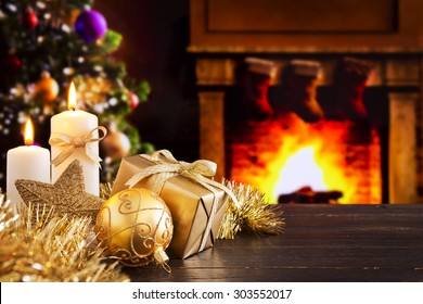 Christmas decorations, a gift and candles in front of a fireplace. A fire is burning in the fireplace and Christmas stockings are hanging on the mantelpiece.