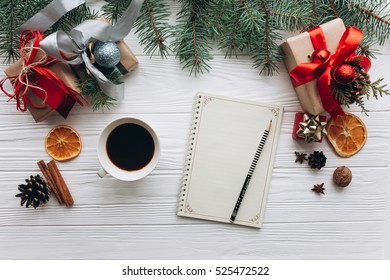 Christmas decorations, gifts and food on a white wooden background. Woman drinking coffee and writing to do list on vintage notebook.