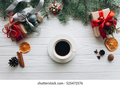 Christmas decorations, gifts and food on a white wooden background. Woman drinking coffee.