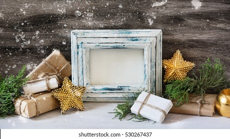Christmas decorations, gifts and photo frame on the grey vintage background.  New year greeting card template. Holiday mock up. Scandinavian style.
