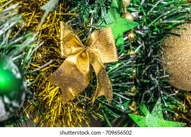 Christmas decorations. Golden Christmas bow on a background of green tinsel. Limited depth of field.