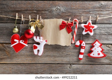 Christmas decorations hanging with blank sheet of paper on rope on wooden background