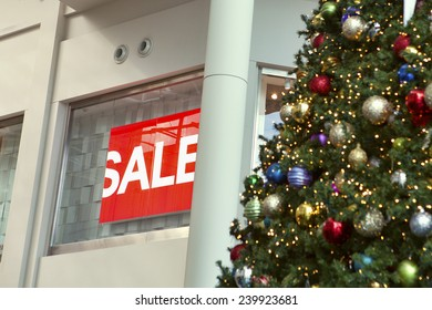 "Christmas decorations hanging in front of a partially hidden ""Sale"" sign during the most lucrative season of the year for retail sales."