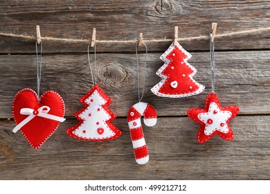 Christmas decorations hanging on rope on wooden background