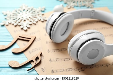 Christmas decorations, headphones and music sheets on blue wooden table, closeup