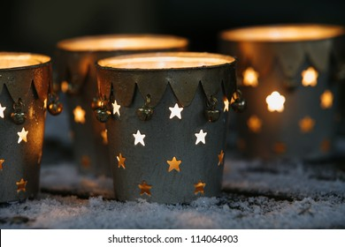 Christmas decorations: holey candle holders on snowy table, closeup