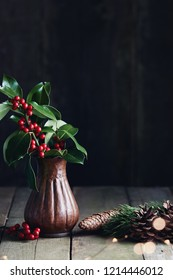 Christmas decorations, holly leaves with fresh red berries in vase.