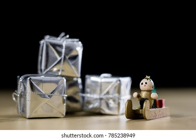 Christmas decorations made of wood on a wooden table. Christmas decorations and small Christmas presents. Black background.