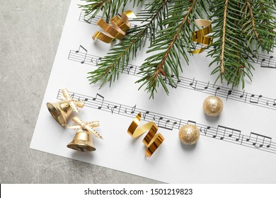 Christmas decorations and music sheet on grey stone table, flat lay