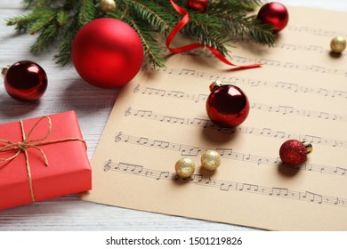 Christmas decorations and music sheet on white wooden table