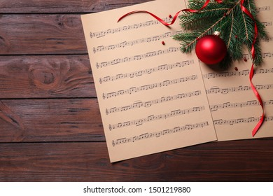 Christmas decorations and music sheets on wooden table, flat lay. Space for text