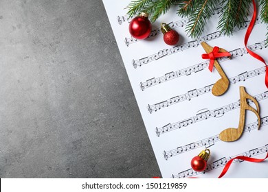 Christmas decorations, notes and music sheet on grey stone table, flat lay with space for text