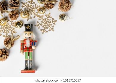 Christmas decorations (nutcracker, snowflakes, bells, pine cones, ...) on a sheet of white paper.