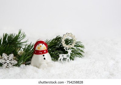 Christmas decorations on a bed of snow. Snowman, reindeer, snowflake and green fir tree branch. White background for copy space.