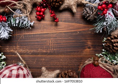 Christmas decorations on a brown wood background with copy space. Pine cones, garland, berries and pine branches