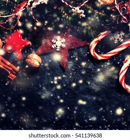 Christmas decorations on dark background, vintage retro style. Winter Xmas card with stars, bells, balls and candies.