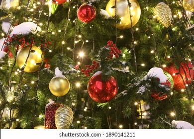 Christmas decorations on the holiday tree.Many colorful balls garland glowing lamps and red berries on the branches are sprinkled with snow.Festive traditional seamless background for the New Year