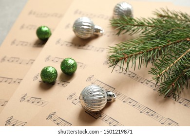 Christmas decorations on music sheets, closeup view