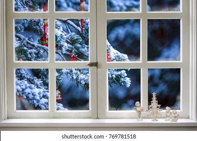 Christmas decorations on a spruce branch, visible through a window. Figures of angels and decorative Christmas tree on the windowsill