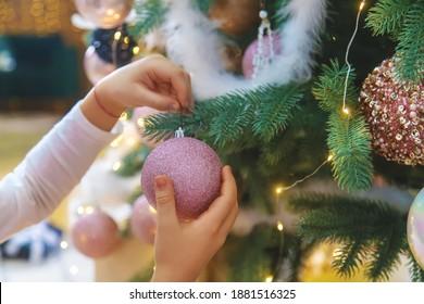 Decoraciones navideñas en el árbol en manos de un niño. Enfoque selectivo.