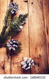 Christmas  decorations on wooden background. Pine cones and fir tree on old wood board with copyspace for greeting text.