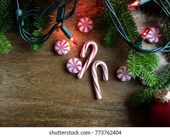 christmas decorations and peppermint candies on a wood surface