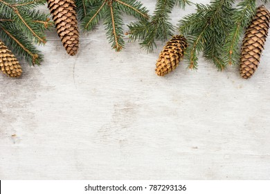 christmas decorations, pine tree branch and cone on white wood