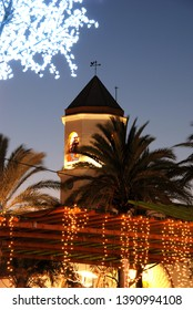 Christmas decorations in a plaza with the Carmen Church bell tower (Parroquia Nuestra Senora del Carmen) to the rear at dusk, Fuengirola, Costa del Sol, Malaga Province, Andalucia, Spain,