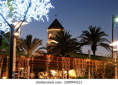 Christmas decorations in a plaza with the Carmen Church bell tower (Parroquia Nuestra Senora del Carmen) to the rear at dusk, Fuengirola, Costa del Sol, Malaga Province, Andalucia, Spain.