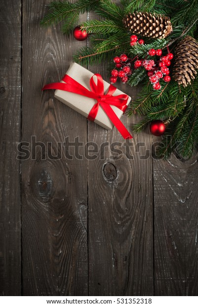 Christmas decorations present fir tree branch pine cones rustic wooden background. Flat lay, greeting card.