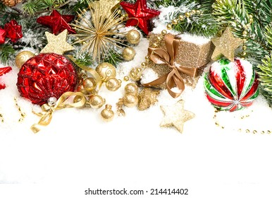 christmas decorations red baubles, golden gift box and pine branches on white background