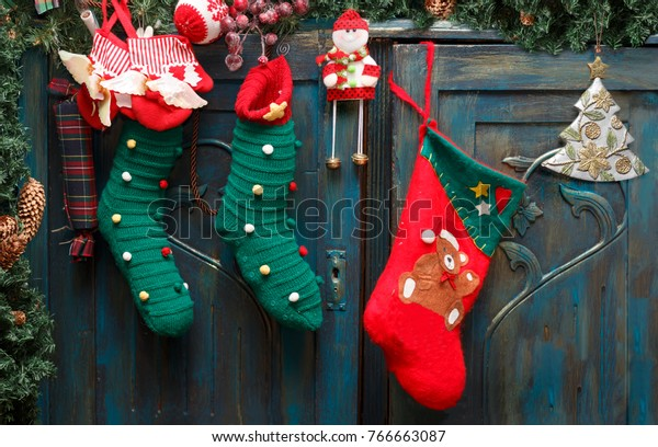 Christmas decorations: red Santa's boot, green stockings, evergreen branch with pine cones and christmas toys on blue doors of old wardrobe.