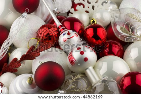 christmas decorations with red white and silver balls and a snowman tree topper