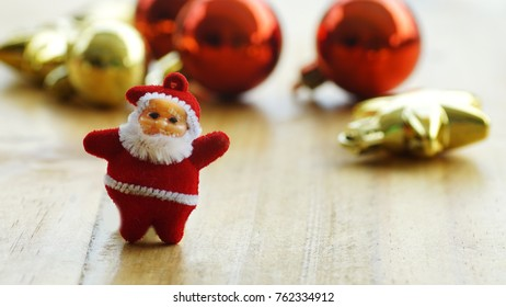 Christmas decorations with a santa claus and a gift present on a wooden background.