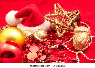 Christmas decorations, Santa Claus hat, balls and nuts on a red