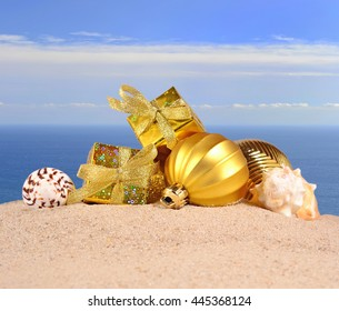Christmas decorations and seashells on a beach sand against the background of the sea